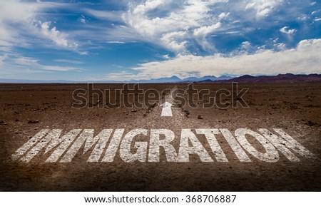 Immigration written on desert road - stock photo