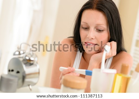 Impatient brunette woman in bathroom waiting for pregnancy test result - stock photo
