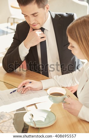 Important points. Vertical shot of a young businesswoman working on papers with her male business colleague over a cup of coffee - stock photo