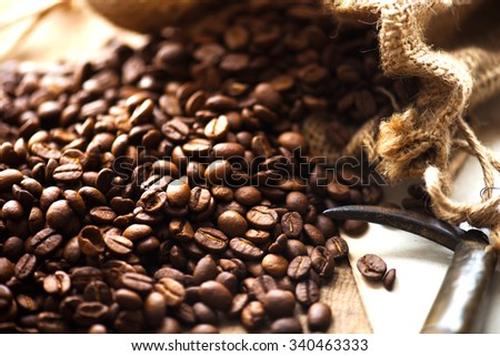 Imported coffee beans spilling out from a hemp sack. Shallow depth of field.  - stock photo