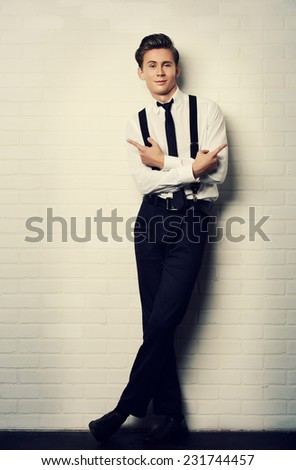 Imposing young man in elegant suit posing by white brick wall. - stock photo