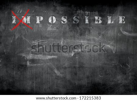 Impossible written with white chalk on a blackboard. - stock photo