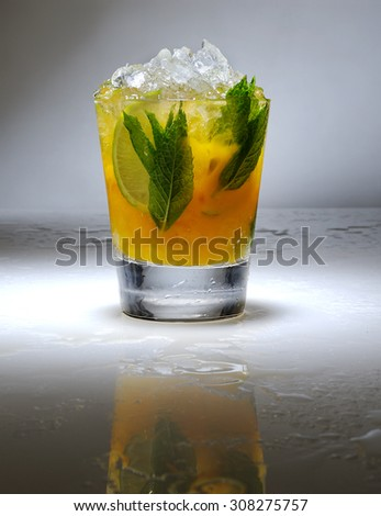 impressive cocktail with crushed is and mint for garnish with reflection on a gradient background with shadows - stock photo