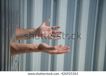 Imprisoned man outstretches arms through prison bars, as though asking for help or food - stock photo