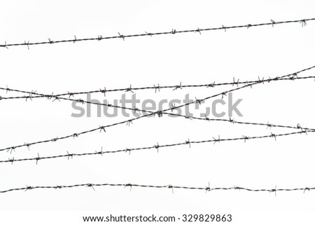 imprisonment, restriction concept - barb wire fence over gray sky - stock photo