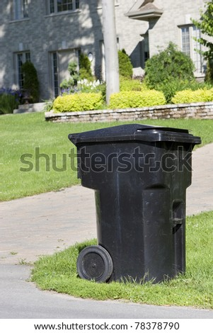 Improperly positioned wheeled garbage can curbside - stock photo