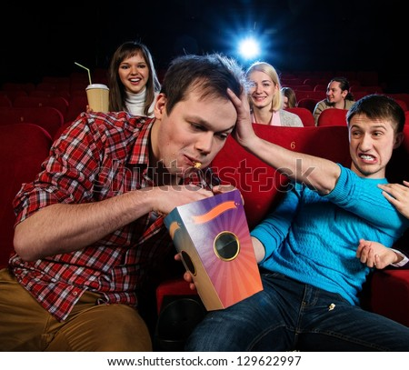 Impudent young man steal popcorn in cinema while people watching movie - stock photo