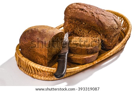 In a basket two small loaves of rye bread, one of the two pieces cut with a knife - stock photo