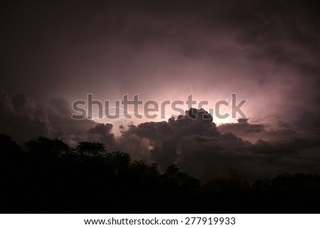 In a flash.  Intense cloud-to-cloud lightning from a summer evening thunderstorm. - stock photo