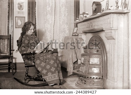 In a heavy robe, a woman reads in front of a coal stove installed in her fireplace. - stock photo