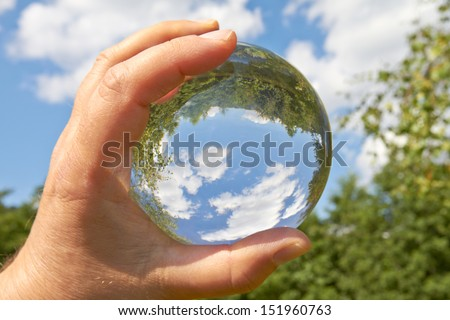 In a held glass ball can you seen the landscape behind her. - stock photo