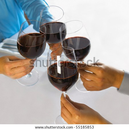 in a restaurant clinking the red wine glasses - stock photo
