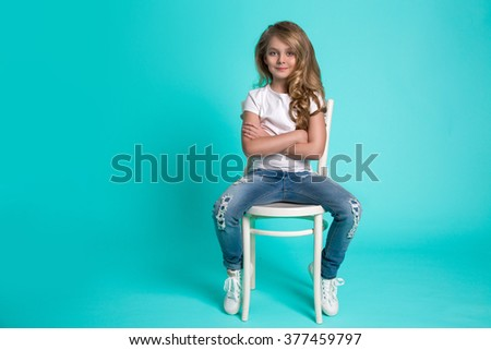 in a white T-shirt and denim pants and sneakers, clothing for children, smiles and feels like a schoolgirl - stock photo