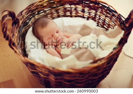 in a wicker basket brown cute sleeping baby - stock photo