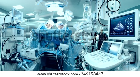 In advanced operating room with lots of equipment, patient and working surgical specialists - stock photo