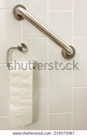 in an invalid toilet is there an bar and toilet paper - stock photo