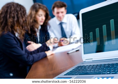 In background happy young business people having meeting at office. In front focus placed on graph showing progress on laptop screen. - stock photo