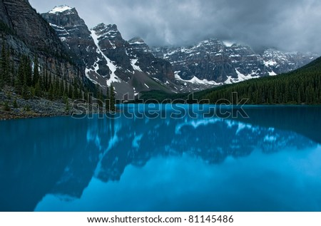 In Banff National Park, Alberta, Canada, Moraine Lake and surrounding mountains (Valley of Ten Peaks) during a gloomy sunrise. - stock photo