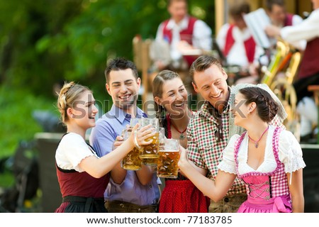 In Beer garden in Bavaria, Germany - friends in Tracht, Dindl and Lederhosen and Dirndl standing in front of band - stock photo