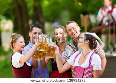In Beer garden in Bavaria, Germany - friends in Tracht, Dirndl and Lederhosen and Dirndl standing in front of band - stock photo
