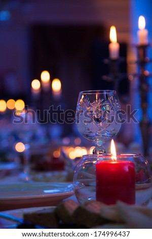In blue light holiday table with candles and a glass - stock photo