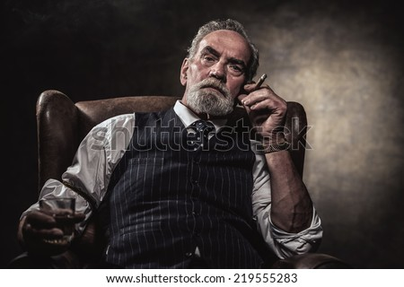 In chair sitting senior business man with cigar and whisky. Gray hair and beard wearing blue striped gilet and tie. Against brown wall. - stock photo