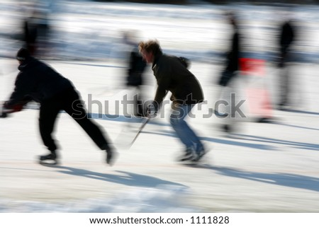 in denmark the winter with people ice skating and playing hockey, low shutter speed and panning - stock photo
