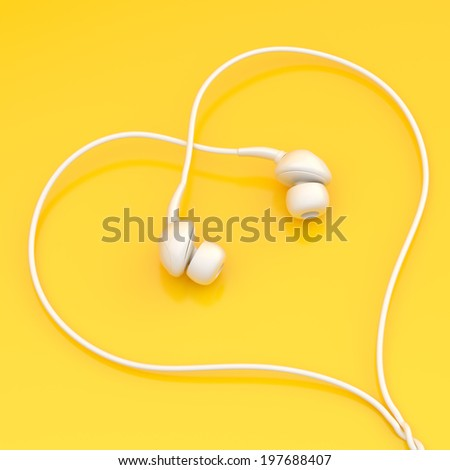 In-ear white headphones forming a heart shape over the yellow surface - stock photo
