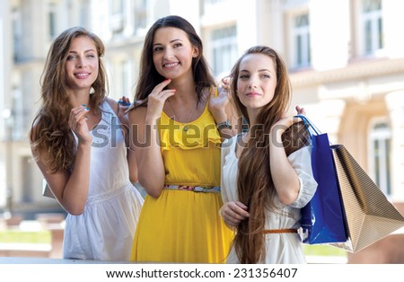 In front of the shop window. Three young and pretty girls are standing in front of shop window while going shopping - stock photo