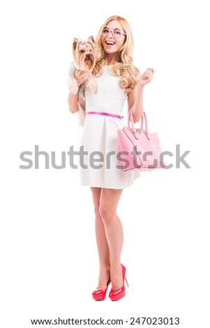 In glamorous style. Full length of attractive young blond hair woman in beautiful white dress carrying Yorkshire terrier and smiling while standing isolated on white background - stock photo