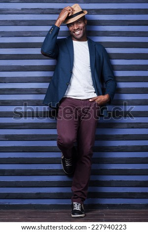 In his own style. Full length of handsome young African man adjusting his hat and smiling while standing against striped background - stock photo