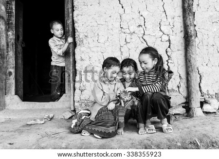 In Lao Cai, Vietnam - September 27th, 2015: Ethnic boy watching his brother frolicking kids, play with the cat loves autumn afternoon in Lao Cai, Vietnam - stock photo