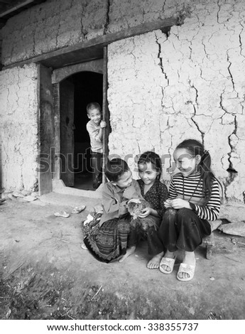 In Lao Cai, Vietnam - September 27th, 2015: The children from ethnic minorities are laughing with cat on hand on autumn afternoon in Lao Cai, Vietnam - stock photo