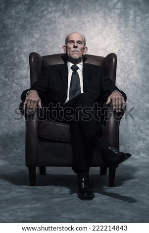 In leather chair sitting senior businessman with gray beard wearing dark suit and tie. Against grey wall. - stock photo