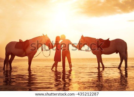 In love couple kissing on the beach. Two horses at sunset, summer scene. sunset in the sea - stock photo