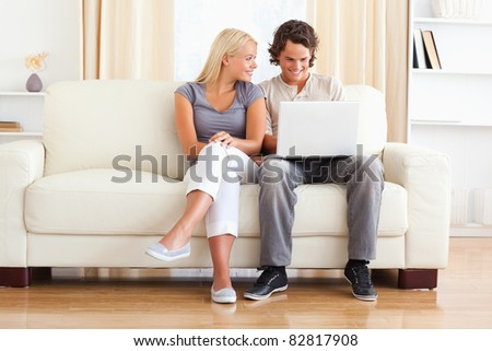 In love couple using a laptop while sitting on a sofa - stock photo