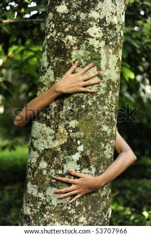 In love with nature: happy woman hugging a tree in the forest - stock photo