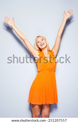 In love with whole world. Beautiful young woman in pretty dress keeping arms raised and smiling while standing against grey background   - stock photo