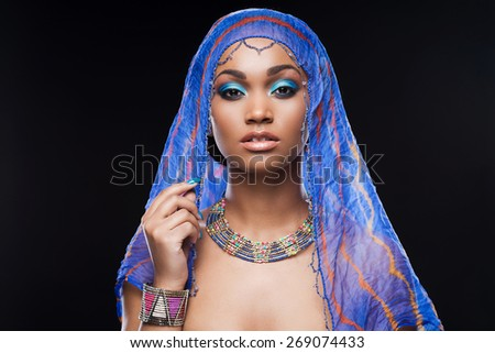 In mysterious style. Beautiful African woman covering head by scarf and looking at camera while standing against black background - stock photo
