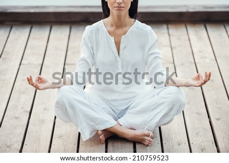In peace and balance with the world. Cropped image of beautiful young woman in white clothing sitting in lotus position and meditating outdoors - stock photo
