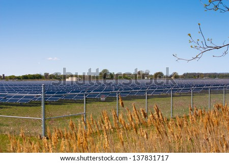 In Sarnia Ontario acres of farmland are covered with solar panels to produce energy from the sun at this large scale solar farm. - stock photo