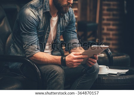 In search of new ideas. Close-up of young bearded man holding digital tablet and sitting in chair  - stock photo