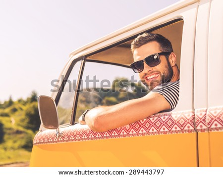 In searching of adventures. Happy young man looking at camera and smiling while sitting at the front seat of his minivan - stock photo