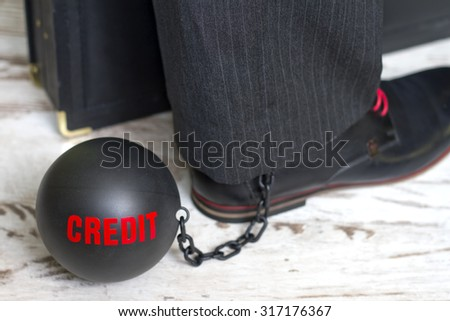 In slavery of credit concept with metal ball on chain and leg - stock photo