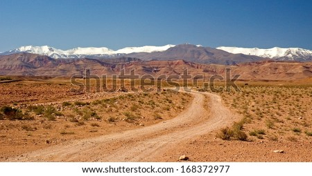In South Morocco, near the village of El Kelaa M'Gouna, a dirt track winds up to the snowy mountains of the atlas - stock photo