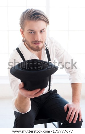 In style. Handsome young man in shirt and suspenders stretching out hand with hat in it and looking at camera while sitting on the chair - stock photo