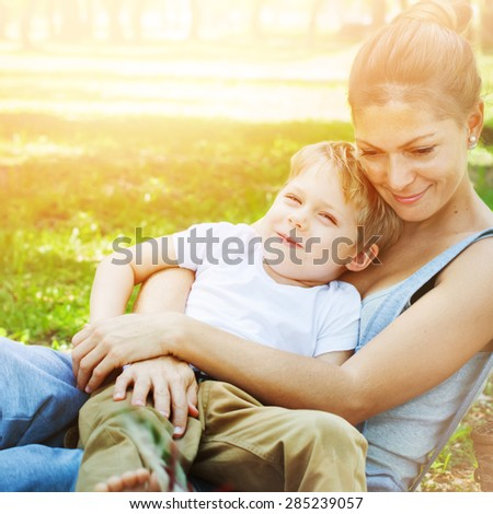 In Sunlight. Mother Embraces the Son. Family in a Spring Park.  - stock photo