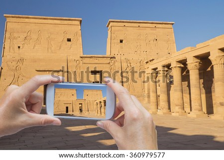 In the bottom left of the photo are hands holding smart phone and taking picture of the Philae Temple dedicated to the Goddess Isis near egyptian city Aswan. (Aswan, Egypt) - stock photo