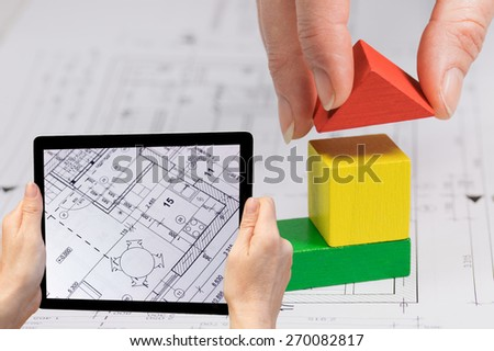 In the bottom left of the photo are hands holding tablet, whose screen contains  photo of blueprint.. Background of the photo contains abstract of construction with color wooden cubes toys. - stock photo