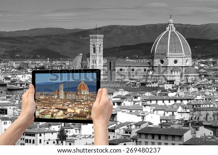 In the bottom left of the photo are hands holding tablet, with photo of the Cathedral Santa Maria del Fiore in Florencel. Background of the photo contains monochromatic  photo of Florence (Italy) - stock photo